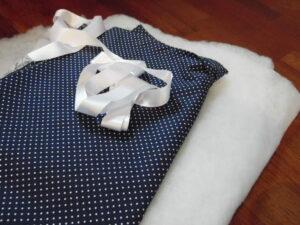 Bandagier Unterlagen nähen: Blau weißer Stoff und eine weiße Schleife