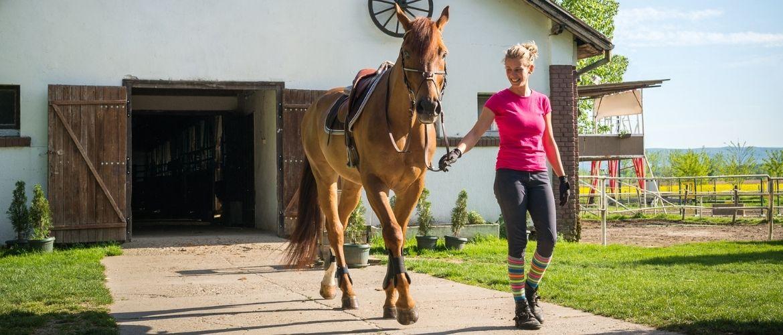 Frau spaziert mit ihrem Pferd aus dem Pferdestall heraus