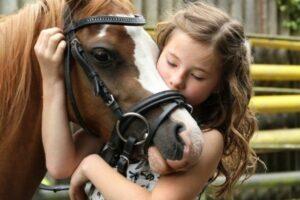 Kinder und Pferde: Junges Mädchen umarmt ihr Pferd
