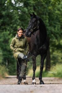 Regenjacke fürs Reiten: Frau mit Pferd in einer Pfütze
